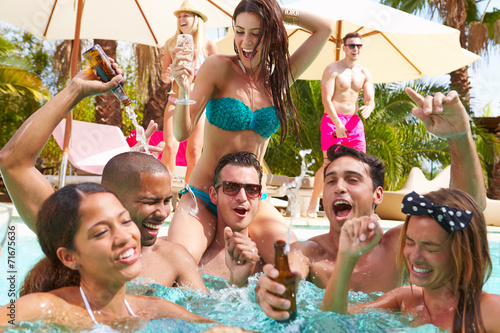 Group Of Friends Having Party In Pool Drinking Champagne - 71675636