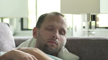 Young man sleeping on sofa at home