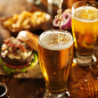 canvas print picture - pouting beer into glass with burgers on wooden table top