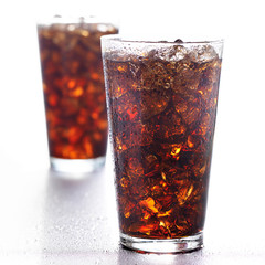 two tall glasses of cola with ice on white background