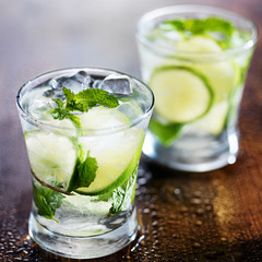 two ice cold fresh mojito cocktails on wooden table