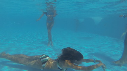 Beautiful slender girls swim underwater