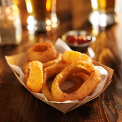basket of crispy onion rings with beer in the backgound