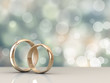 A pair of gold wedding rings with bokeh background - 71677272