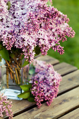 Bouquet of lilac flowers in vase on wooden background