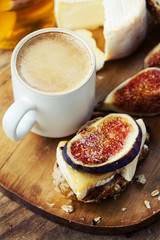Breakfast setting with coffee, bread, cheese, figs and honey