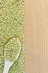 Lentils green on board on the left with spoon