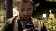 Man texting, sending sms on smartphone at night
