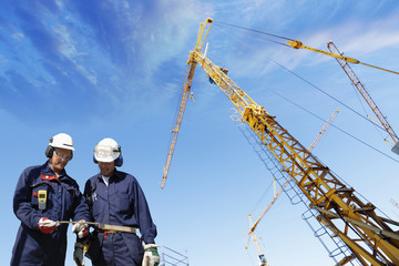 construction workers and giant mobile cranes