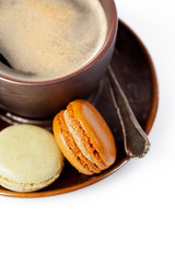 Cup of coffee and macaroons on white background