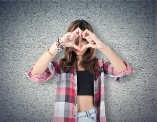 Girl making a heart with her hands over textured background