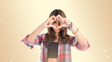 Girl making a heart with her hands over ocher background