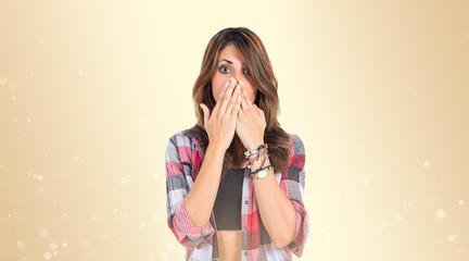 Girl doing surprise gesture over ocher background