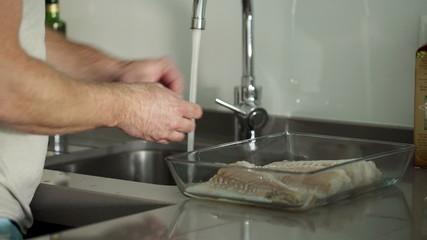 Man preparing, washing fish fillet in sink