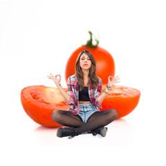 Pretty girl in zen positionaround tomatoes