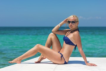 Blonde model on the boat deck posing in sunglasses