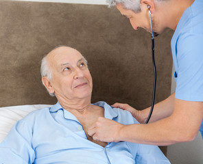 Senior Man Looking At Caretaker Examining Him With Stethoscope