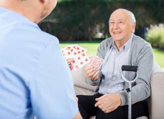 Caretaker And Senior Man Playing Cards At Nursing Home