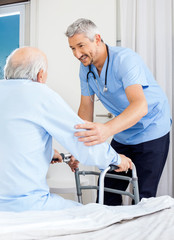 Caretaker Assisting Senior Man To Use Walking Frame