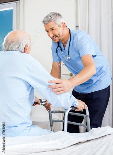 Caretaker Assisting Senior Man To Use Walking Frame - 71680681