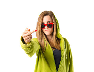 Girl making horn gesture over white background