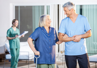 Happy Nurse Assisting Senior Woman To Walk
