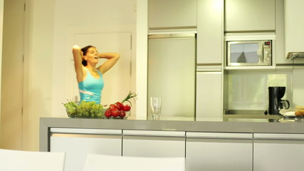 Woman walk into home after jogging, drinking juice