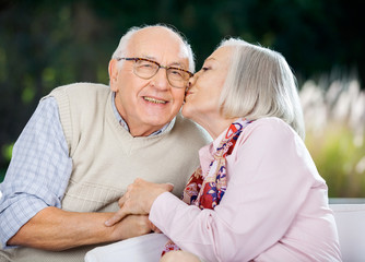 Senior Woman Kissing On Man's Cheek