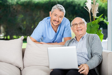 Happy Nurse And Senior Man With Laptop