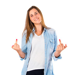 Girl making horn gesture over white background