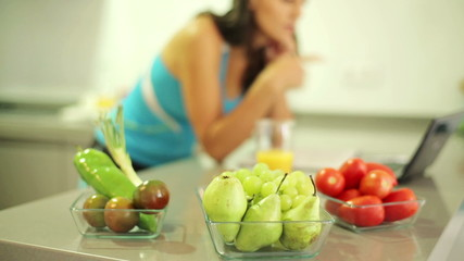 Bowls of fruits and vegetables, sporty woman in background
