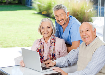 Caretaker And Senior Couple With Laptop At Nursing Home