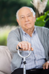 Portrait Of Senior Man Holding Metal Walking Stick
