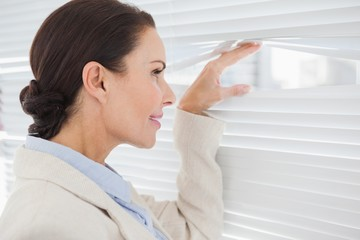 Businesswoman looking through some blinds