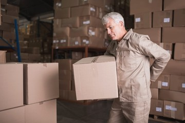 Worker with backache while lifting box in warehouse
