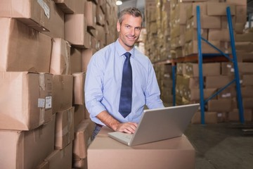 Portrait of warehouse manager using laptop