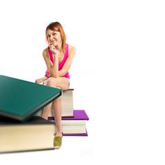 Redhead girl sitting on books