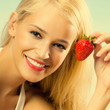 Young smiling woman with strawberry on beach
