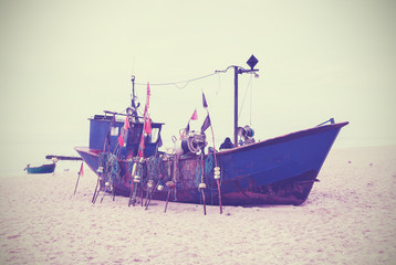 Small fishing boat on shore of the Baltic Sea, vintage retro sty