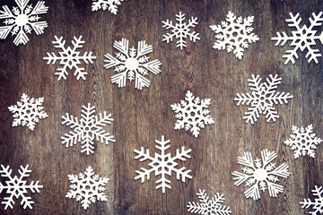 Christmas background with various paper snowflakes on wooden sur
