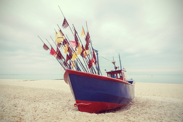Fishing boat on beach, vintage retro filtered.