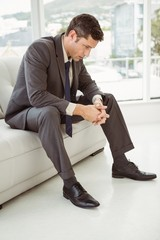 Worried businessman sitting on couch
