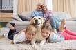canvas print picture - Parents watching children on rug with labrador