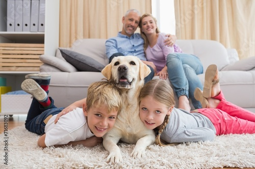 canvas print picture Parents watching children on rug with labrador
