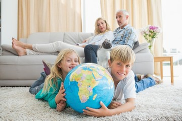 Siblings looking at globe on the floor