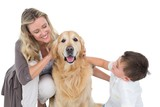 Smiling mother and son petting their golden retriever poster
