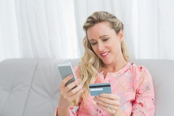 Woman looking at her credit card holding phone