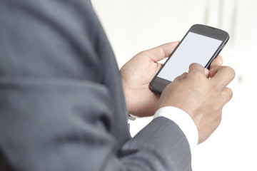 Businessman holding smartphone with blank screen