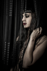 Beautiful and sexy nude brunette woman behind a curtain of black