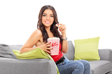 Beautiful girl eating popcorn seated on a sofa